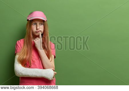 Attractive Thoughtful Pretty Redhead Girl Looks Aside And Thinks Deeply About Something, Wears Cast