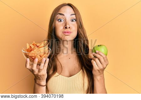 Young brunette woman holding nachos and healthy green apple puffing cheeks with funny face. mouth inflated with air, catching air.