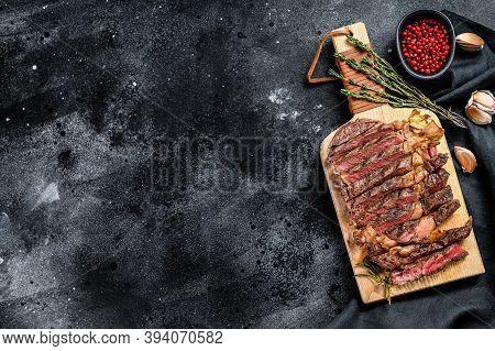 Grilled Rib Eye, Ribeye Steak On A Chopping Board, Medium Rare. Marbled Meat. Black Background. Top