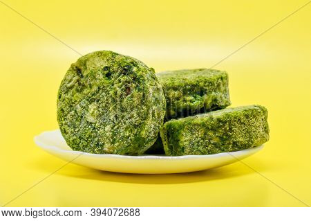 Green Vegetable Cutlets In A Plate On A Yellow Background. Frozen Vegetarian Cutlets Made From Veget