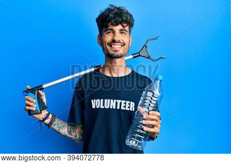 Young hispanic man holding plastic bottle and litter picker to recycle smiling with a happy and cool smile on face. showing teeth.