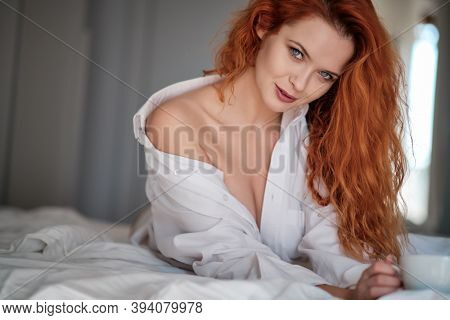 cute red hair woman in white shirt relax on the bed in her white room