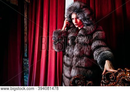 Winter fur coat fashion. Portrait of a gorgeous fashionable woman posing in a silver fox fur coat in a luxury apartment.