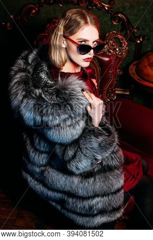 Luxury lifestyle. Portrait of a gorgeous fashionable woman posing in a silver fox fur coat and sunglasses in a luxury apartment. Fur coat fashion.