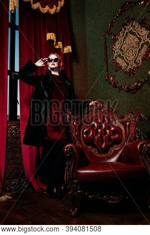 Luxury lifestyle. Portrait of a stunning fashionable woman posing in a luxury mink fur coat and sunglasses in a rich vintage apartment. Fur coat fashion.