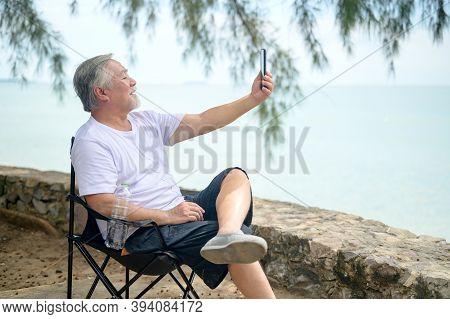 Asian Senior Man Sitting Next To The Beach Alone. Retirement Age Using Mobile To Video Call With Fam