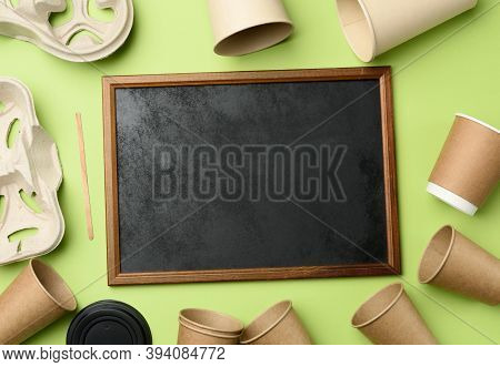 Wooden Frame And Disposable Paper Cups From Brown Craft Paper And Recycled Paper Holders On A Green