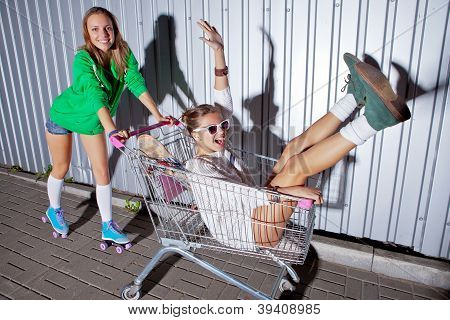 a beautiful young girl in sexy shorts and roller scates is pushing a supermarket trolley with a laughing girl. they both are projecting shadows onto the wall poster