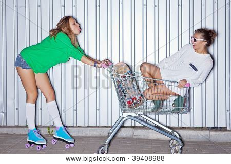 two beautiful young girls with a scateboard, roller scates and a supermarket trolley