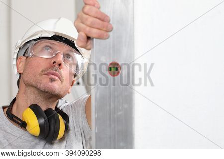 Man Worker Looks At The Spirit Level Checks The Wall With Hard Hat, Glasses And Ear Protection Headp