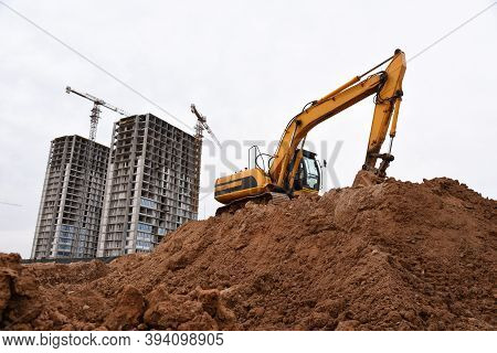 Excavator During Earthmoving At Construction Site. Backhoe Dig Ground For The Construction Of Founda