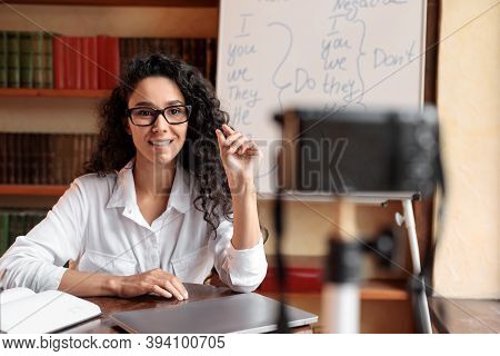 Online Lesson. Young Female English Language Professor In Glasses Sitting At Desk, Teaching Grammar