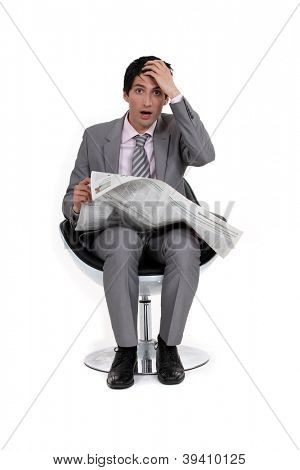 A businessman reading bad news.