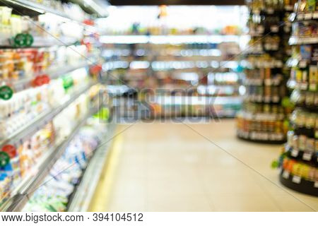 Blurry Supermarket Background, Grocery Store Aisle With Food Products On Shelves. Abstract Blurred D