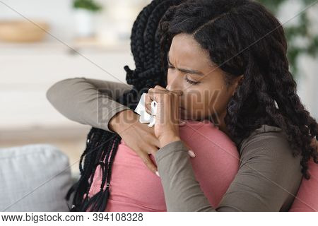 Closeup Of Crying Black Woman Hugging Her Girlfriend Or Sister, Home Interior, Copy Space. Unrecogni