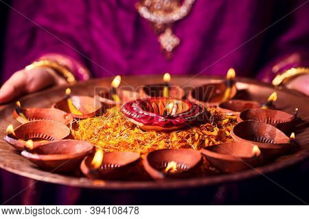 Happy Diwali Background. Indian Woman Or Bride Wearing Traditional Cloth And Jewelry, Holding Puja T