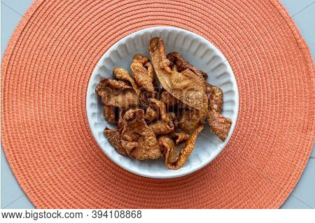 Thai Traditional Snacks, Crispy Fried Chicken Skins In A White Bowl On Red Background. Snack And App