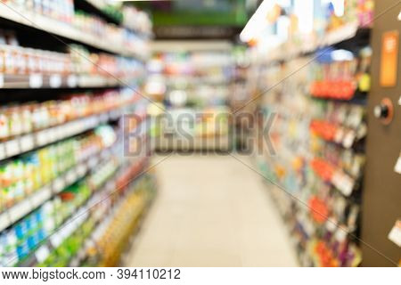 Blurred Supermarket Background, Grocery Store Aisle With Colorful Shelves And Food Products. Shoppin