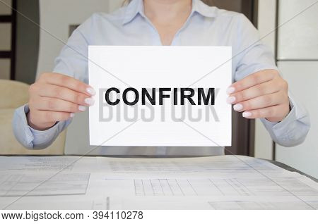 The Word Confirm Is Written On A White Notebook Held By A Girl
