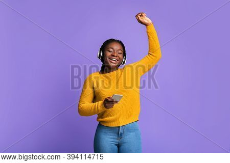 Listen Music Online. Carefree Black Woman With Wireless Headphones And Smartphone Dancing With Close