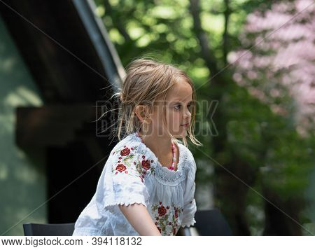 Portrait Of Beautiful 5 Years Old Girl In The Sumer Time On The Blurry Background Of Green Garden.