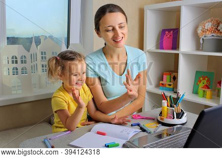 Mother And Little Kid Sit At The Kitchen Table Studying Online Together. Mom And Little Girl Handwri