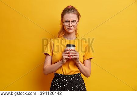Displeased Beautiful European Woman With Tail Frowns Face And Has Offended Expression, Drinks Take A
