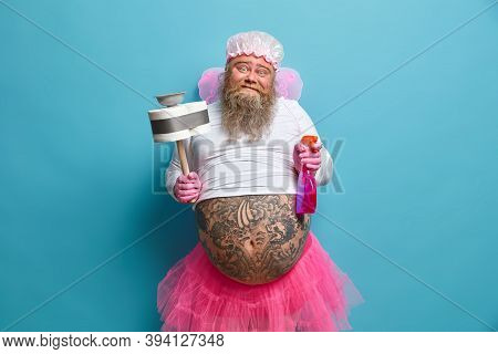 Spring Cleaning And Housekeeping Concept. Positive Bearded Fairy Of Cleanliness Holds Spray Detergen