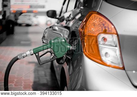 Man At A Petrol Pump Fuel Station Inserting Nozzle Into Fuel Tank Of A Car And Starting The Fuel Pum