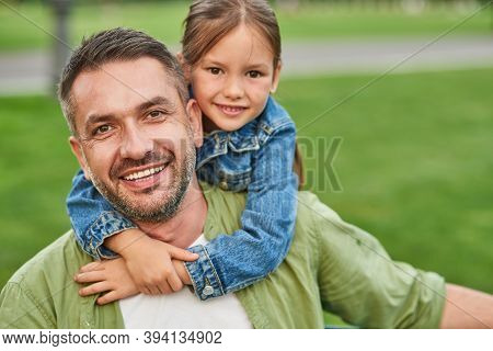 Portrait Of Young Joyful Father And His Cute Little Daughter Looking At Camera And Hugging While Spe