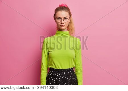 Half Length Shot Of Confident Serious Schoolgirl Ready For School, Looks Directly At Camera, Has Pon
