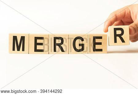 Word Merger. Wooden Small Cubes With Letters Isolated On White Background With Copy Space Available.
