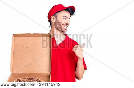 Young hispanic man holding delivery pizza box pointing thumb up to the side smiling happy with open mouth