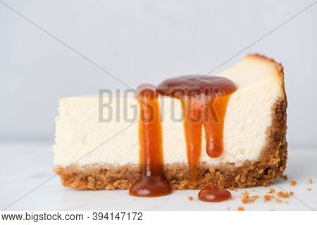 Slice Of Cheesecake With Salted Caramel Sauce On Grey Background, Closeup View. Perfect Cheesecake W