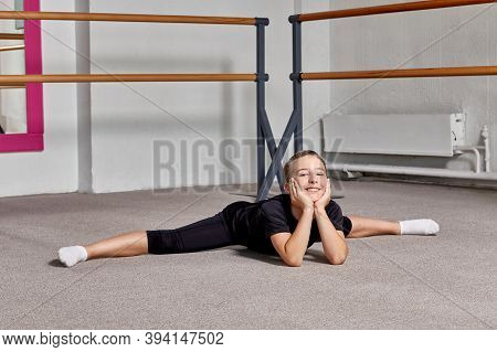 Guy Sitting On A Splits On The Carpet At Ballet School, Looking At The Camera.