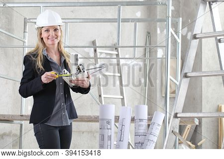 Smiling Woman Architect Or Construction Interior Designer With With Meter Measuring White Windows Cu