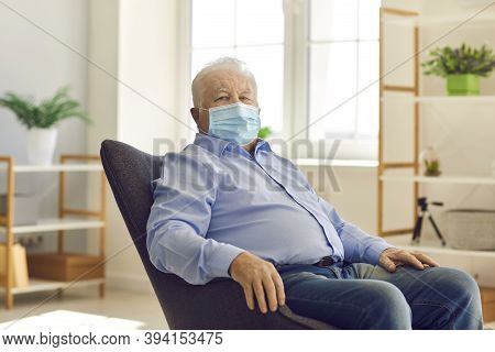 Serious Senior Citizen Wearing Medical Face Mask Looking At Camera Sitting In Armchair At Home