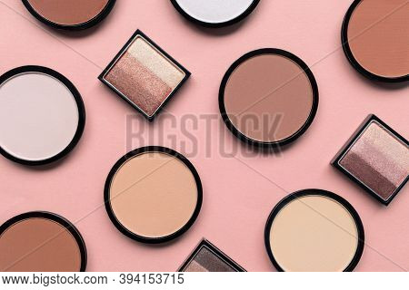 Cosmetic Products For Makeup On Pastel Pink Background. Beige Eyeshadow, Blush And Face Compact Powd