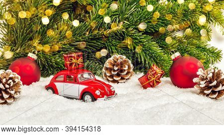 Fulda, Germany - October 24, 2020: Red Car In Snow With Pine Cones, Christmas Baubles, Gifts, Fir Tr