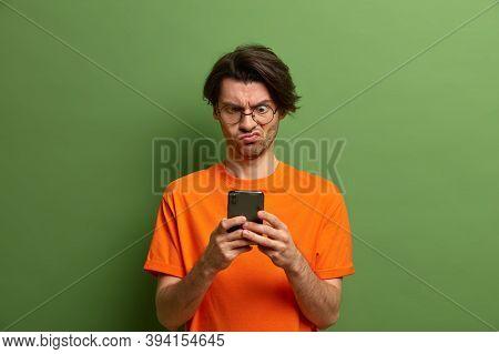 Handsome Man In Glasses Looks With Displeasure At Smartphone Screen, Got Upset After Receiving Unple