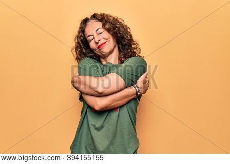 Middle age beautiful woman wearing t-shirt with red star revolutionary symbol of communism hugging oneself happy and positive, smiling confident. Self love and self care