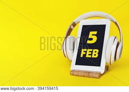 February 5th. Day 5 Of Month, Calendar Date. Stylish Headphones And Modern Tablet On Yellow Backgrou