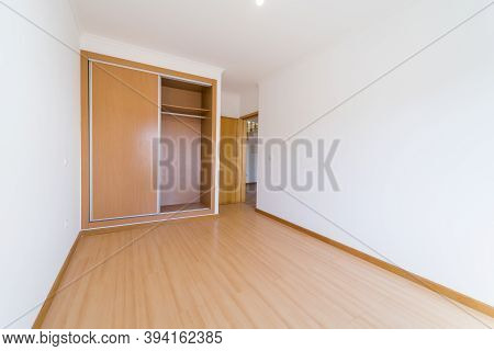 Empty Room With Dark Wooden Floating Laminate Flooring And Wardrobe. House Interior, Wide Bedroom Sp