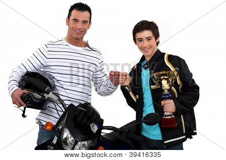 Father congratulating son on motocross victory