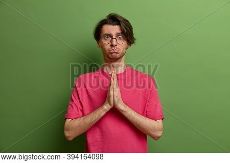 Sad Adult Man With Imploring Look, Keeps Palms Pressed Together, Prays With Hope And Face, Begs Desp