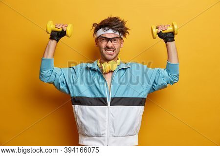 Weight Lifting, Power And Strength Concept. Funny Active Man Puts Efforts In Lifting Dumbbells, Pose