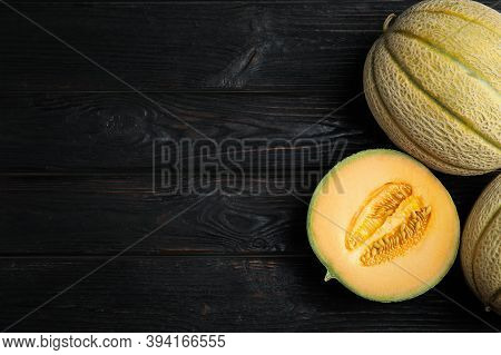 Tasty Fresh Melons On Black Wooden Table, Flat Lay. Space For Text