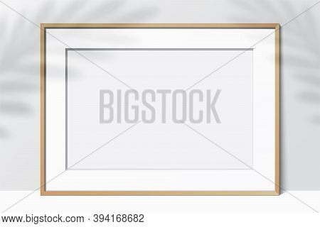 Horizontal Wooden Frame, Standing On A White Background With Leaf Shadows. Blank Elegant Frame Templ