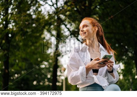 Low-angle Shot Of Cheerful Young Woman Browsing Internet On Smartphone, Looking Away. Portrait Of Fe