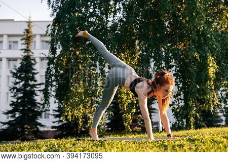 Low-angle Shot Of Young Woman Practicing Yoga In Down Facing Dog Pose On One Leg, City Park At Sunny